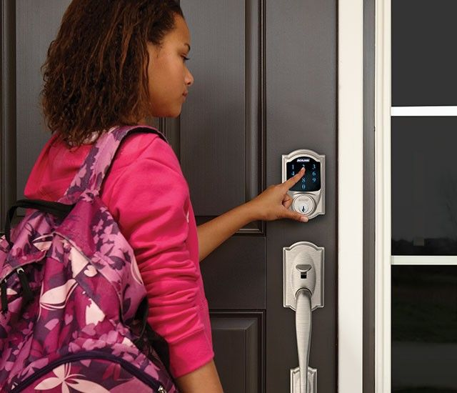 image of a young woman operating a Schlage smart lock on her home's front door